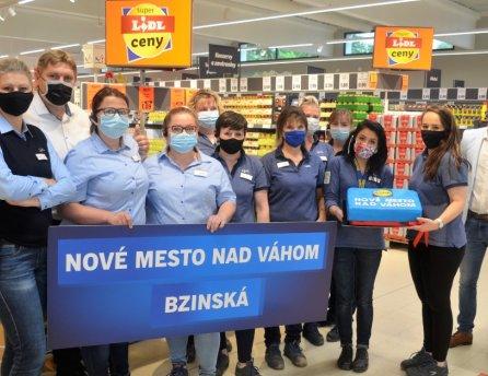 Zamestnanci novej predajne Lidl, otvorenej v Novom Meste nad Váhom s tortou a bannerom